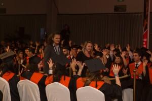 María Teresa Brioso, guiada por su guía-intérprete, atraviesa un pasillo de estudiantes que aplauden en lengua de signos